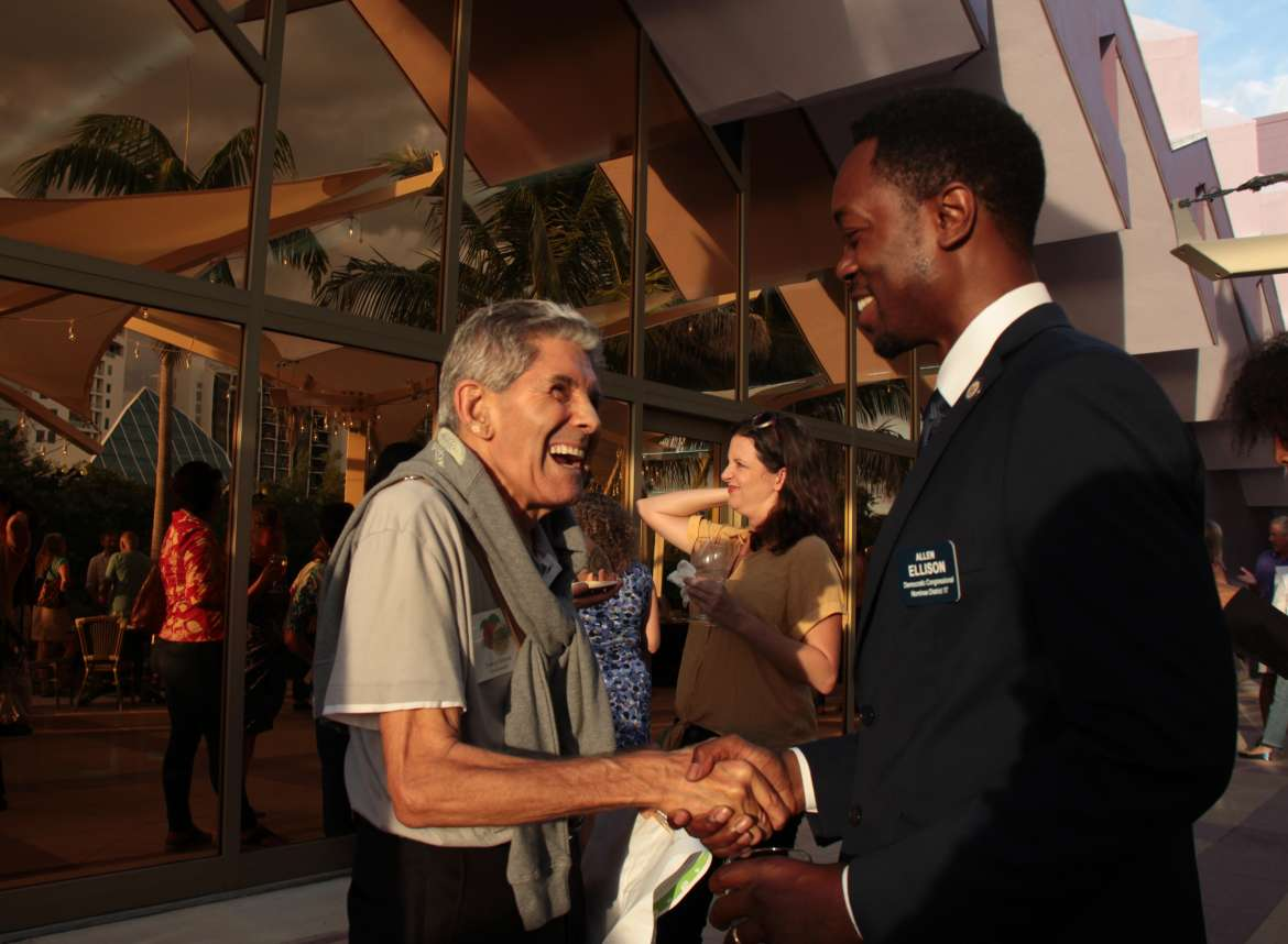 allen shaking hands with an elderly supporter inside during an event