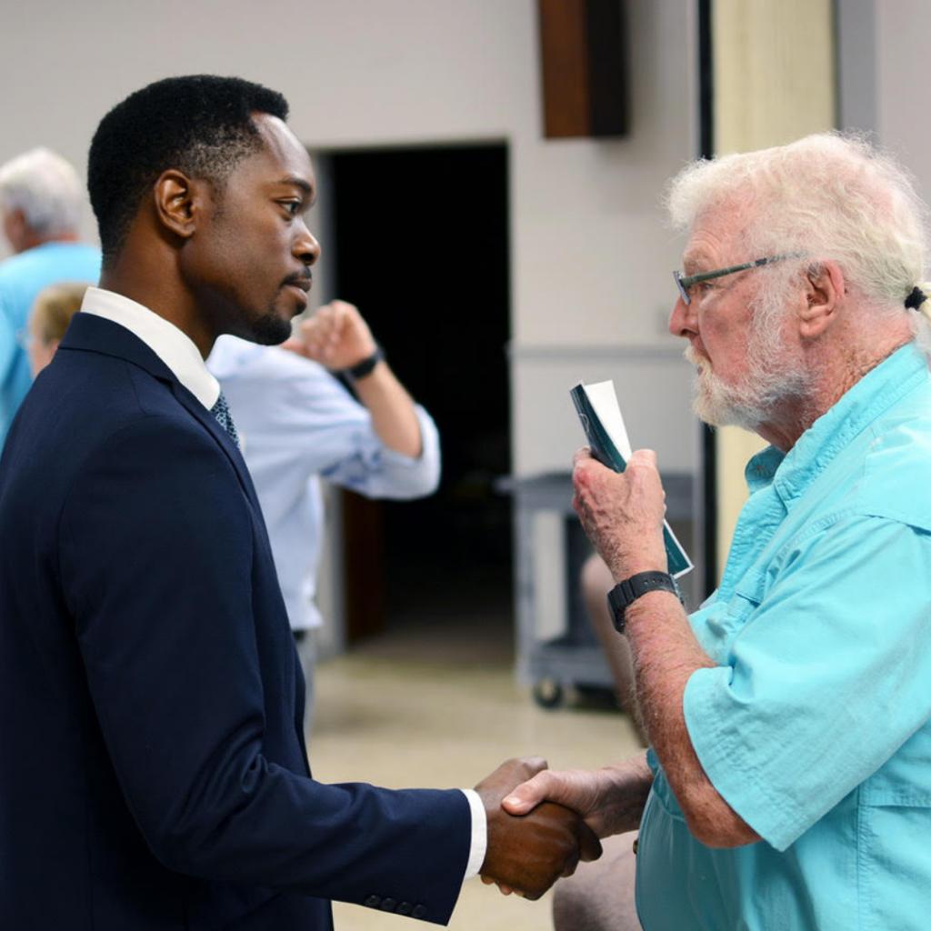 allen talking to an older Caucasian gentleman shaking his hand